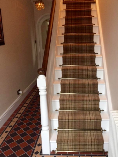 Ulster Beaumont Axminster carpet finished with Dubai antique brass stair rods.